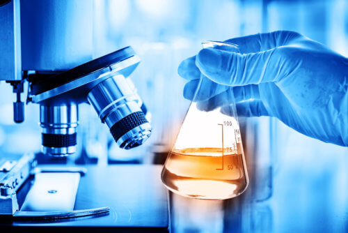 Flask in scientist hand with lab microscope background in laboratory. Science or chemical research and development concept